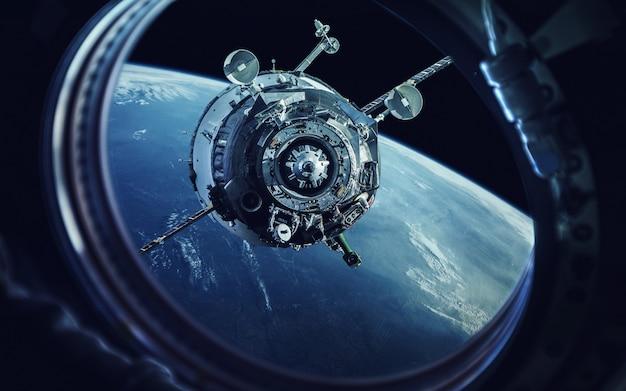 Uitzicht vanaf de patrijspoort van het ruimteschip. aarde en ruimtevaartuigen.
