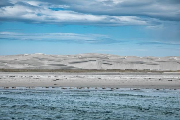 Uitzicht vanaf de sombere zee op grijze duinkust en cloudscape, zee van cortes, baja california, mexico