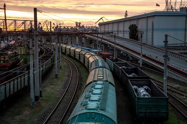 Uitzicht vanaf de spoorbrug naar goederentreinen bij zonsondergang.