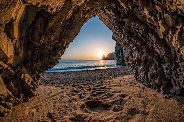 Uitzicht vanaf de stenen grot op de zonsondergang zee en het strand