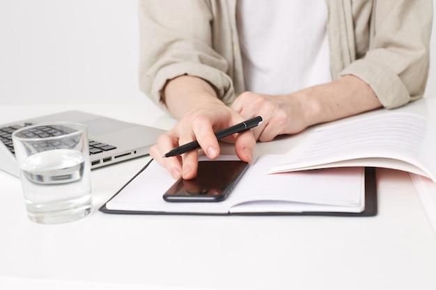 Uitzicht vanaf de top op jonge man met pen in de hand maken van aantekeningen