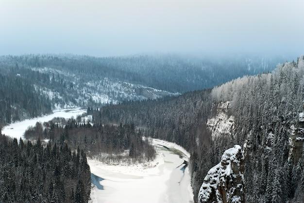 Uitzicht vanaf de top van de rots naar de bevroren rivier die tussen de kliffen in het winterlandschap stroomt