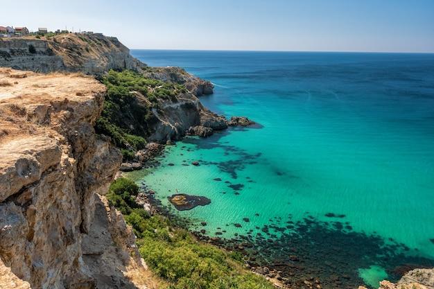 Uitzicht vanaf de top van de rots op kristalheldere zee zonnige dag heldere hemel