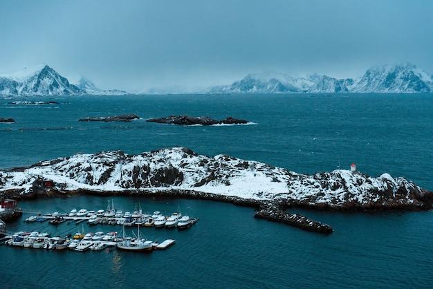 Uitzicht vanaf de top van een klein vissersdorpje met veel boten op de ligplaats. noorse koude zee die de kusten van eilanden spoelt. verbazingwekkende details van de lofoten-eilanden.