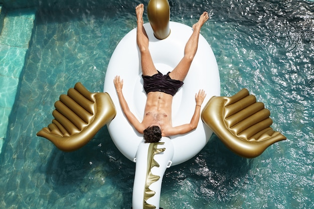 Uitzicht vanaf de top van jonge blanke man met aantrekkelijk gespierd lichaam ontspannen shirtless op grote opblaasbare matras, drijvend in zwembad met blauw water, dutje doen en zonnebrand krijgen op warme dag