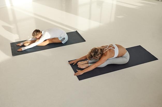 Uitzicht vanaf de top van twee jonge mensen, man en vrouw met gespierde flexibele lichamen die sportkleding dragen die samen yoga beoefenen, zittend op matten, paschimottasana doen. sport, gezondheid en flexibiliteit
