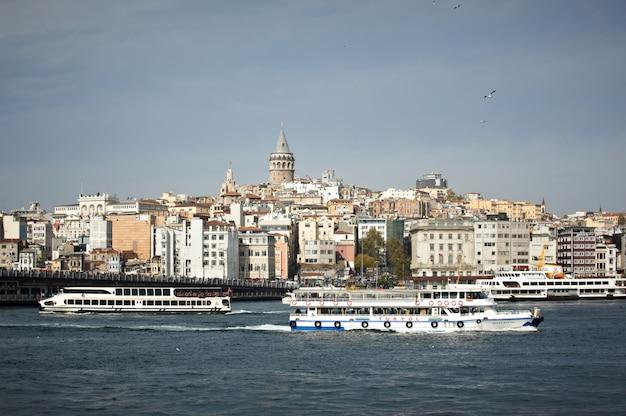 Uitzicht vanaf de zee naar de stad istanbul, galata tower, golden horn, boten, heuvels en meeuwen. kalme zee