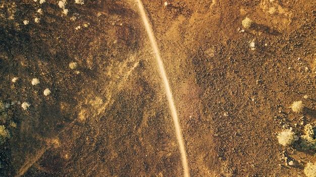 Uitzicht vanaf het gedreun van het woestijnlandschap met een pad erdoorheen, dor landschap met weinig begroeiing