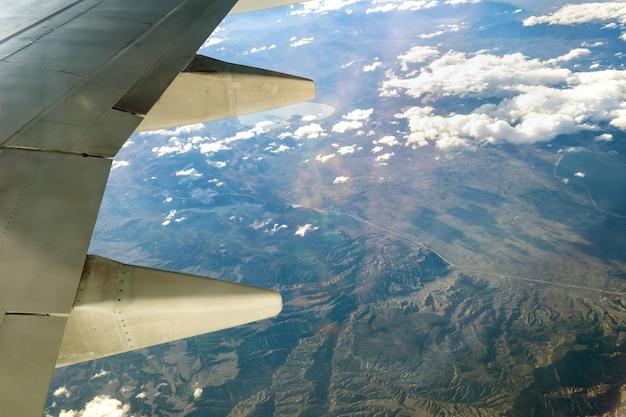 Uitzicht vanaf het vliegtuig op de witte vleugel van het vliegtuig die over bewolkt landschap in zonnige ochtend vliegen. vliegreizen en transport concept.