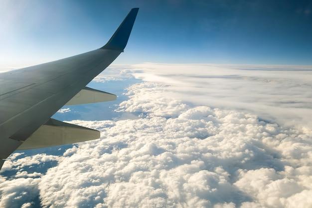 Uitzicht vanaf het vliegtuig op de witte vleugel van het vliegtuig die over bewolkt landschap in zonnige ochtend vliegen.