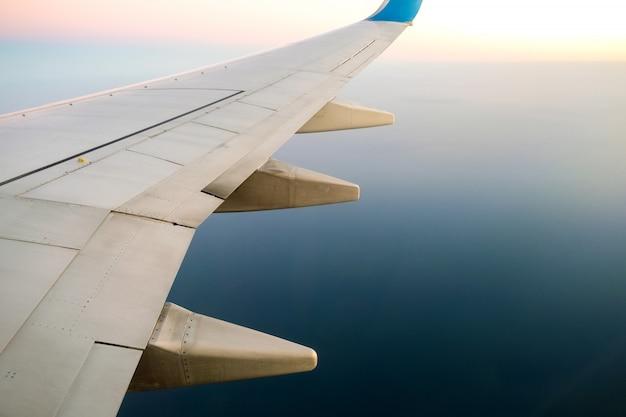 Uitzicht vanaf het vliegtuig op de witte vleugel van het vliegtuig die over oceaanlandschap in zonnige ochtend vliegen. vliegreizen en transport concept.