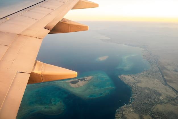 Uitzicht vanaf het vliegtuig op de witte vleugel van het vliegtuig die over oceaanlandschap in zonnige ochtend vliegen.