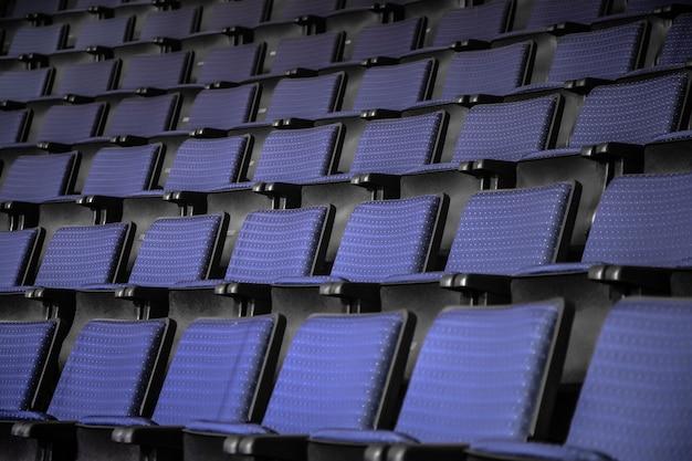 Uitzicht vanaf trappen op rijen comfortabele blauwe stoelen in theater of bioscoop. curve van blauwe stoelen