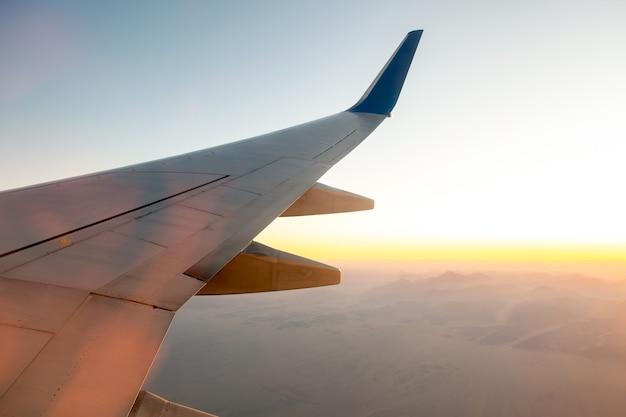 Uitzicht vanaf vliegtuig op de witte vleugel van het vliegtuig vliegen over woestijnlandschap in zonnige ochtend. vliegreizen en transport concept.
