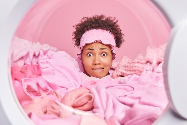 Uitzicht vanaf wasmachine van nerveuze huisvrouw met krullend haar heeft angstige uitdrukking bijt lippen verdronken in stapel wasgoed draagt hoofdband druk bezig met huishoudelijk werk