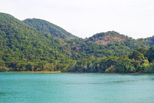 Uitzicht vanaf zee naar de bergen met de jungle op het eiland