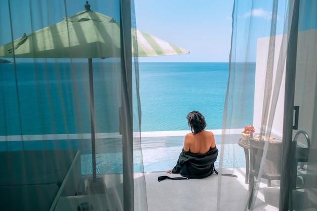 Uitzicht vanuit de hotelkamer van een vrouw die bij het overloopzwembad zit
