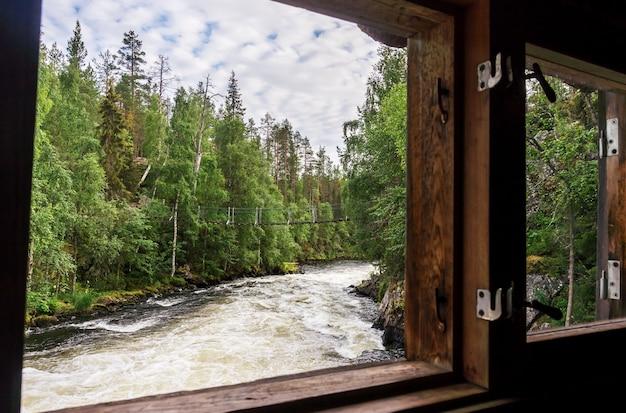 Uitzicht vanuit het raam van een oude molen op een hangbrug, finland. oulanka nationaal park