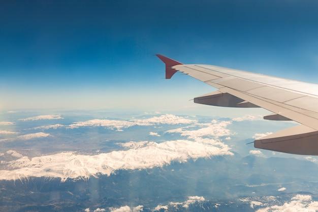 Uitzicht vanuit het raam van het vliegtuig dat over de bergen vliegt