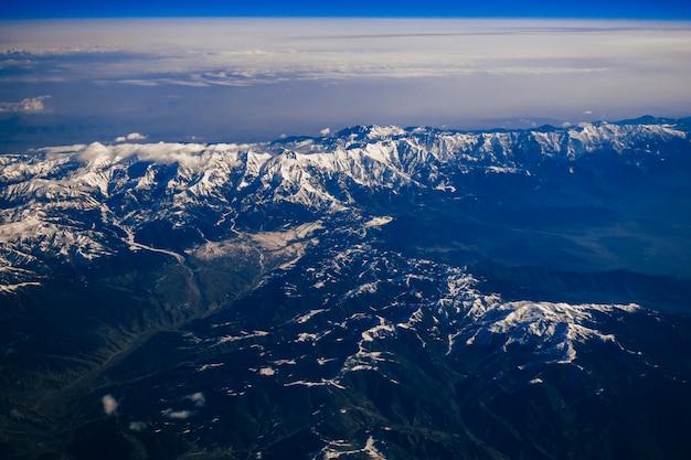 Uitzicht vanuit het raam van het vliegtuig op de bergen met besneeuwde toppen