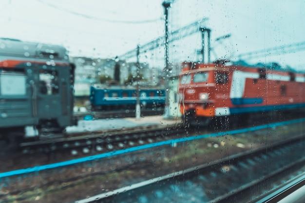 Uitzicht vanuit het treinraam bij regenachtig weer.