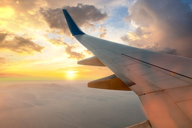 Uitzicht vanuit het vliegtuig op de witte vleugel van het vliegtuig die in zonnige ochtend over woestijnlandschap vliegt.