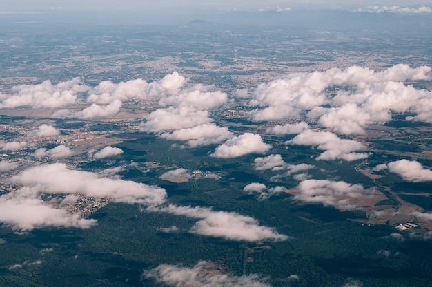 Uitzicht vanuit het vliegtuigraam naar de grond hieronder door witte wolken