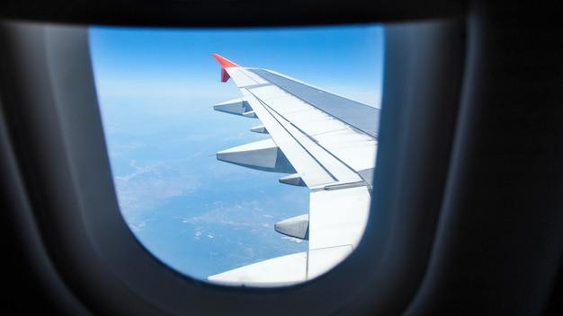 Uitzicht vanuit het vliegtuigraam op vleugel en aarde.