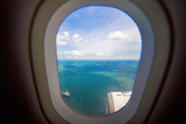 Uitzicht vanuit raam van vliegtuig naar zee en vrachtschepen zorgeloos uitzicht vanuit patrijspoort landingsvliegtuig