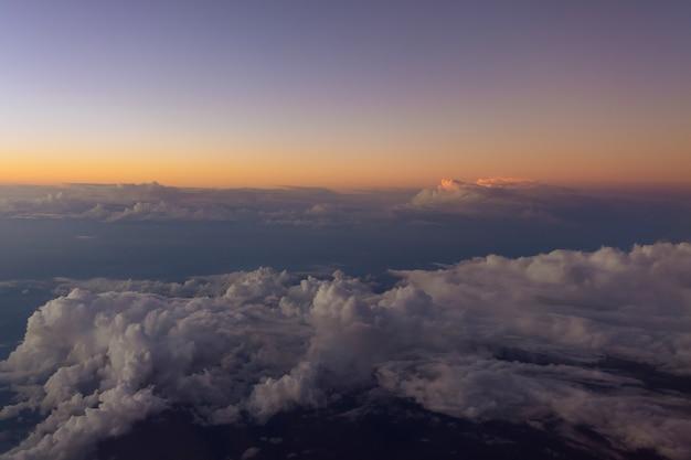 Uitzicht vanuit vliegtuig prachtige zonsonderganghemel boven wolken met dramatisch licht het vliegtuigraam