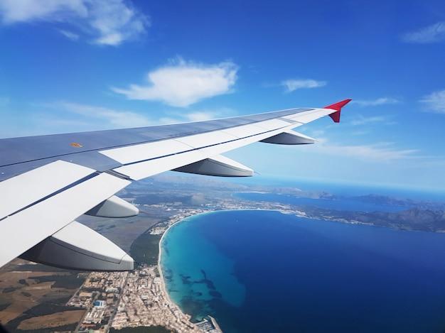 Uitzicht vanuit vliegtuig raam, vleugel van een vliegtuig vliegen boven tropisch eiland.