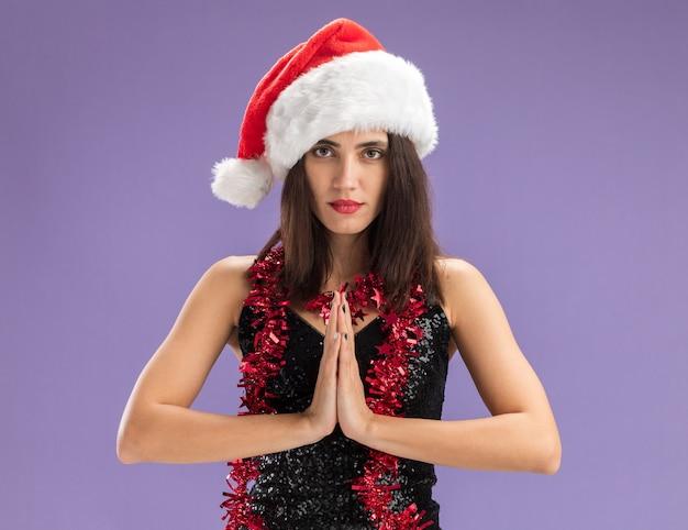 Uitziende camera jong mooi meisje met kerstmuts met slinger op nek tonen bidden gebaar geïsoleerd op paarse achtergrond