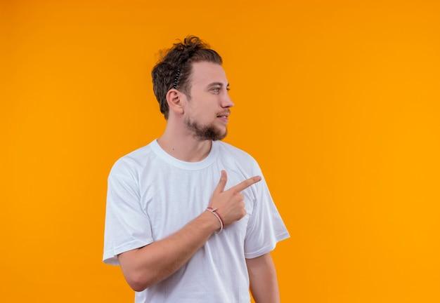 Uitziende jonge kerel die een wit t-shirt draagt, wijst naar de zijkant op geïsoleerde oranje achtergrond
