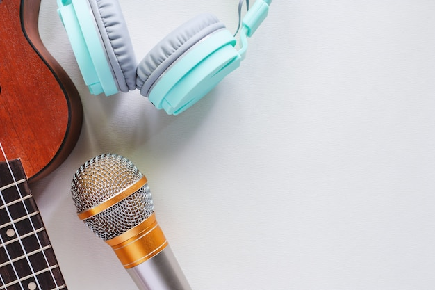 Ukelele met groene hoofdtelefoons en microfoon op witte achtergrond