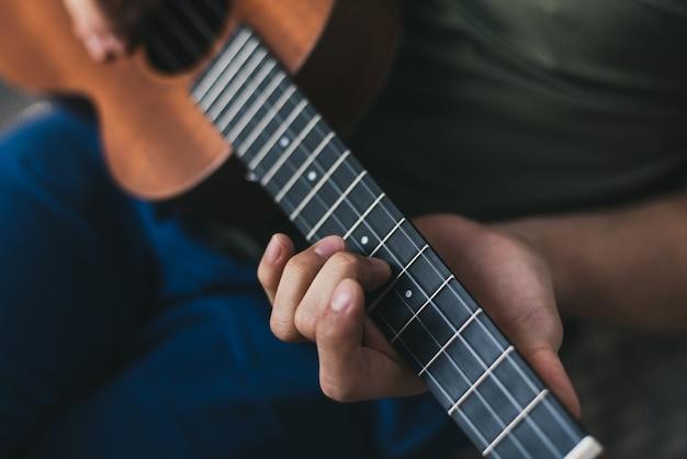 Ukelele spel. een man die een beetje gitaar speelt. de artiest schrijft de muziek thuis op de ukelele