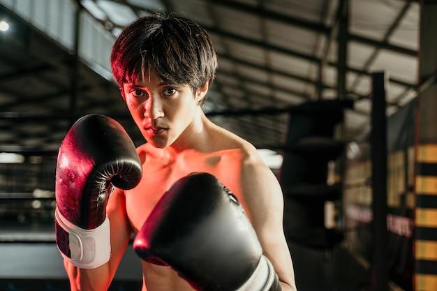 Ultieme vechter in bokshandschoenen met beweging hand in hand op rode verlichting naast copyspace op de ringarena