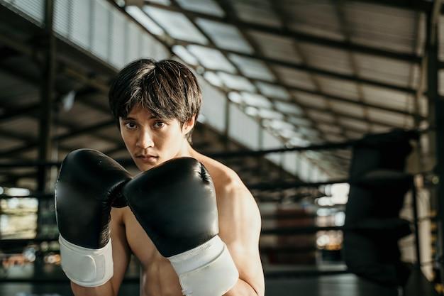 Ultieme vechter in bokshandschoenen met bewegingshanden verdedigen naast copyspace op de ringarena