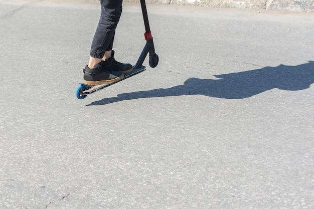 Ulyanovsk, rusland - 20 april 2019: kinderen rijden gevaarlijk op scooters op de rijbaan. scooter rijden. verkeersveiligheid. geen veilig voetgangersgedrag. zonnige dag. schaduwen op de stoep.