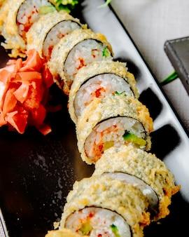 Unagi maki tempura komkommer rijstpaling roomkaas gember zijaanzicht