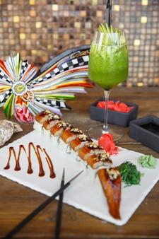 Unagi sushi rolt geserveerd op witte stenen bord met kiwi cocktail