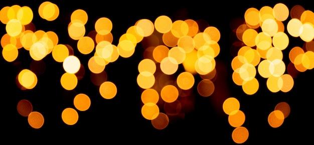 Unfocused abstracte gouden bokeh op zwarte achtergrond