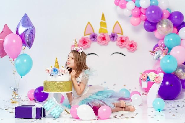 Unicorn girl poseren in de buurt van gelukkige verjaardagstaart. idee voor het versieren van een verjaardagsfeestje in eenhoornstijl. eenhoorndecoratie voor festivalfeestmeisje