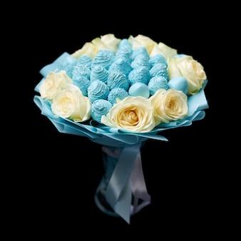 Uniek boeket van witte rozen en rijpe aardbeien bedekt met blauwe chocolade staat in een vaas op een zwarte achtergrond