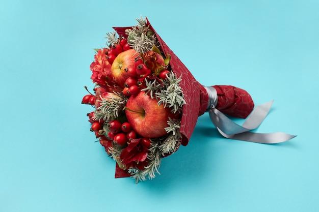 Uniek cadeau in de vorm van een rood boeket bloemen en fruit op een blauwe achtergrond