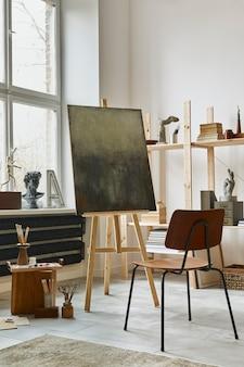 Uniek interieur van de kunstenaarswerkruimte met stijlvolle teakhouten commode, houten ezel, boekenkast, kunstwerken, schilderaccessoires, decoratie en elegante persoonlijke spullen. moderne werkkamer voor kunstenaar.