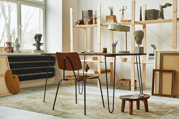 Uniek interieur van een kunstenaarswerkruimte met stijlvol bureau, houten ezel, boekenkast, kunstwerken, schilderaccessoires, decoratie en elegante persoonlijke spullen. moderne werkkamer voor kunstenaar.