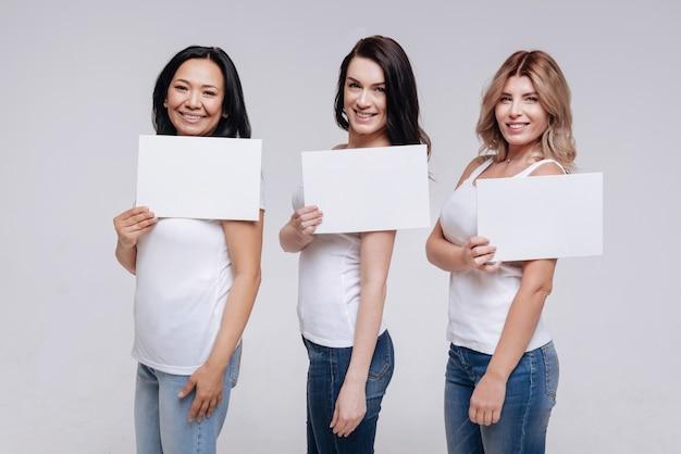 Uniek is mooi. actieve charismatische, verleidelijke vrouwen met stukjes papier in hun handen