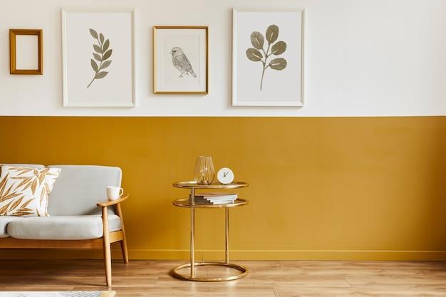 Unieke woonkamer in modern interieur met design bank, elegante gouden salontafel, lijsten, bloemen in vaas, decoratie en persoonlijke accessoires in woondecoratie.