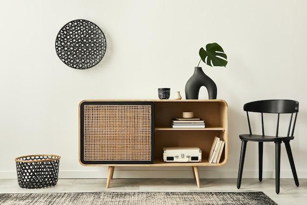 Unieke woonkamer in modern interieur met design houten commode, zwarte stoel, rotan decoratie, kopieerruimte, boek, tapijt en elegante accessoires in woondecoratie.
