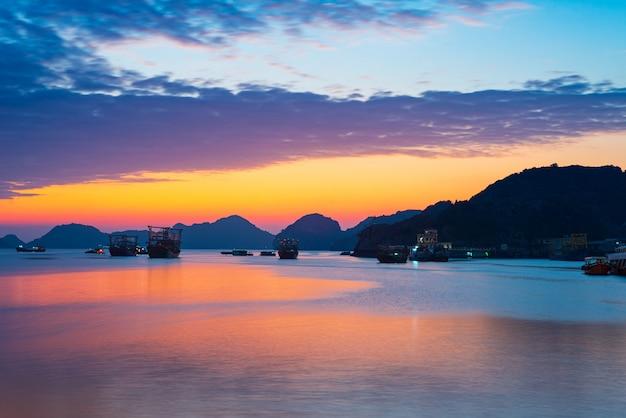 Unieke zonsonderganghemel in de baai van vietnam cat ba met drijvend vissersbootdorp op overzees, cloudscape tropisch weer, lange blootstelling vage motie.